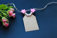 Flowers, clothespins, paper for writing on a dark background. Concept of congratulations on the holiday stock image