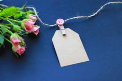 Flowers, clothespins, paper for writing on a dark background. Concept of congratulations on the holiday stock photos