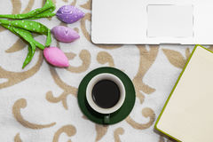 Flowers and coffee with notebook and computer on sofa. Beautiful flowers and coffee on sofa with notebook and computer Royalty Free Stock Images