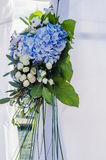 Flowers composition on luxury arch ceremony decorated with lush leaves, white hydrangea, delicate cream roses, purple eustoma, blu Stock Image