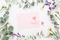 Flowers composition. Paper blank, carnation flowers, eucalyptus branches on pastel  background. Flat lay, top view, copy spaceFlat stock photo