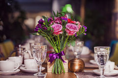 Flowers composition in restaurant,  roses and irises, combination shades of purple Stock Image