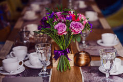 Flowers composition in restaurant,  roses and irises, combination shades of purple Royalty Free Stock Photography
