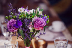 Flowers composition in restaurant,  roses and irises, combination shades of purple Royalty Free Stock Photo