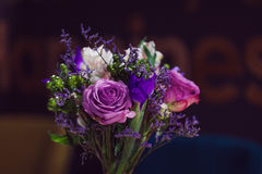Flowers composition in restaurant, roses and irises, combination shades of purple Stock Photography