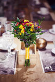 Flowers composition in restaurant, roses and irises, combination shades of purple Royalty Free Stock Image