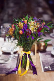 Flowers composition in restaurant, roses and irises, combination shades of purple Stock Photo