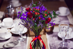 Flowers composition in restaurant, small red roses and purple irises, combination of multiple colors Stock Photos