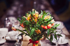 Flowers composition in restaurant, small red roses and purple irises, combination of multiple colors Stock Images