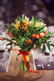 Flowers composition in restaurant, small red roses and purple irises, combination of multiple colors Stock Photo