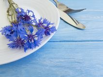 Flowers cornflowers menu catering arrangement service , plate, fork knife on a wooden background. Flowers cornflowers plate fork knife on a wooden background stock image