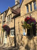 Flowers on a Cotswold wall. Blue sky over the Cotswolds Royalty Free Stock Image