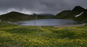 Flowers of crocus in the foreground along Scaffaiolo Lake is a lake in the provinces of Pistoia Tuscany and Modena Emilia-Romag. Scaffaiolo Lake is a lake in the Royalty Free Stock Photography