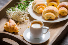 Flowers, croissant and coffee for breakfast Stock Images