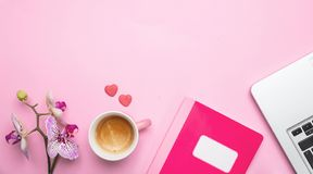 Flowers,  cup of coffee and laptop on pink desk background, copy space. Woman desk office. Flowers,  cup of coffee and computer laptop on pink desk background stock images