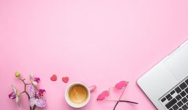 Flowers,  cup of coffee and laptop on pink desk background, copy space. Woman desk office. Flowers,  cup of coffee and computer laptop on pink desk background stock photography