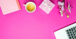 Flowers,  cup of coffee and laptop on pink desk background, copy space. Womens day. Flowers, gift box and computer laptop on pink desk background, copy space stock photography