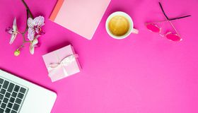 Flowers,  cup of coffee and laptop on pink desk background, copy space. Womens day. Flowers, gift box and computer laptop on pink desk background, copy space royalty free stock photography