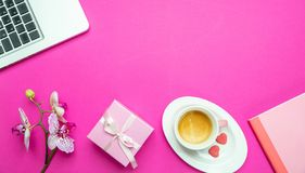 Flowers,  cup of coffee and laptop on pink desk background, copy space. Womens day. Flowers, gift box and computer laptop on pink desk background, copy space royalty free stock photo