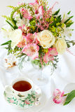 Flowers and cup of tea. Beautiful flowers in vase , cup of tea and biscuits royalty free stock photos