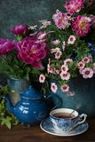 Flowers and cup of tea. Beautiful flowers in vase and cup of tea at wooden table, summer decor royalty free stock photo