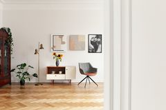 Flowers on cupboard between gold lamp and grey chair in white apartment interior with plant. Real photo stock images