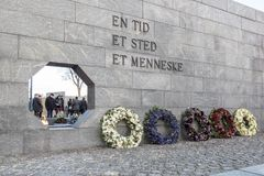 Flowers at Danish National Monument of Remembrance after the fun. Inscription: One Moment, One Place, One Person. The eternal flame seen through an octagonal Stock Photo