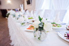 Flowers decor on table of newlyweds at wedding hall. Stock Photo