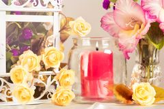 Flowers in decorative cage and candle. Royalty Free Stock Photos
