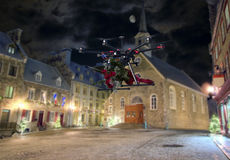 Flowers delivery Drone. A drone making delivery of a bouquet of red roses above empty streets of old city Royalty Free Stock Image