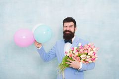 Flowers delivery. Gentleman romantic date. Birthday greetings. Confidence and charisma. Man bearded gentleman suit bow. Tie hold air balloons and bouquet royalty free stock images