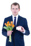 Flowers delivery - man in suit holding tulips Stock Image