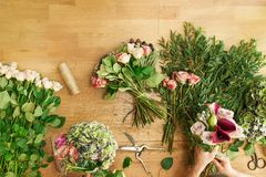 Florist in flower shop delivery make rose bouquet, table top view royalty free stock images