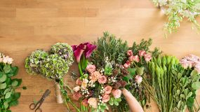 Florist in flower shop delivery make rose bouquet, table top view royalty free stock image