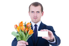 Flowers delivery - young man in business suit holding tulips and Royalty Free Stock Photo