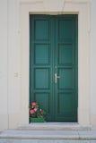 Flowers on doorstep. Red flowers on door step of a closed green door stock photo