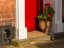 Flower Pot on Doorstep. Flowers in a pot on the doorstep of a house in an English town stock image