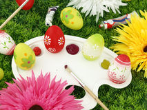 Flowers and Easter eggs on palette Royalty Free Stock Image