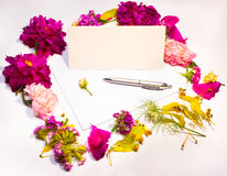 Flowers, envelope and pen on a lilac Stock Images