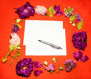 Flowers, envelope and pen on a red Royalty Free Stock Photography