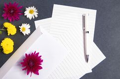 Flowers and envelopes in black background stock photography