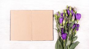 Flowers eustoma and an open diary with empty pages. Book and flowers on a white table. Royalty Free Stock Photos