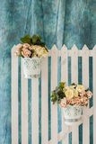 Flowers on the fence. Decoration for wedding, flowers in decorative baskets on the fence, wedding photo area Royalty Free Stock Image