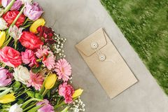 Flowers on florist`s worktable. Natural envelope next to colorful flowers on a florist`s worktable before valentine`s day Royalty Free Stock Photography