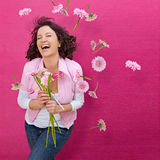 Flowers flowers flowers 3. Happy girl with lots of flowers in front of a pink wall Stock Photos