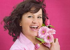 Flowers flowers flowers 5. Happy girl with flowers in front of a pink wall Royalty Free Stock Photography