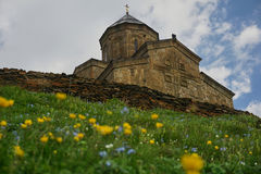 Flowers in foreground. Gergeti Trinity Church in background with Stock Photos