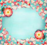 Flowers frame with roses and petals on turquoise blue shabby chic background, top view Royalty Free Stock Photos