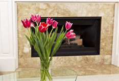 Flowers in front of fire place Royalty Free Stock Image