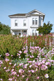 Flowers in Front of Old Victorian Farmhouse. (in Public Park Royalty Free Stock Photo